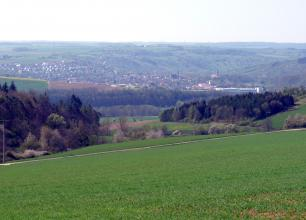 Blick über eine nach links abfallende Grünfläche mit Waldflächen im Mittelgrund. Im Hintergrund, nach einem wieder aufsteigenden Hang, liegen eine größere Ortschaft sowie teils bewaldete Höhen.