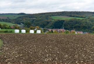 Blick über einen sehr steinigen braunen Acker auf eine von bewaldeten Hügeln und Hochflächen eingeschlossene Ortschaft.
