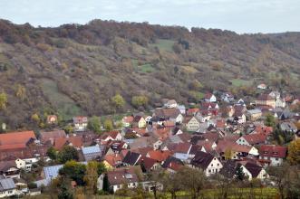 Das Bild zeigt einen oberhalb einer Siedlung zum Hintergrund hin aufsteigenden, größtenteils bewaldeten Hang. Zwischen den Bäumen sind aber auch Steinhügel und Heckenstreifen erkennbar.