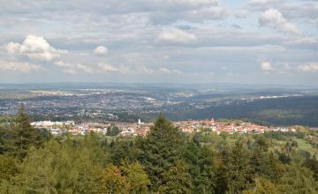 Blick aus großer Höhe über Baumwipfel und bewaldete Bergrücken. Im Hintergrund breitet sich eine größere Stadt aus. Im Mittelgrund, auf einem Bergsattel, liegt eine Ortschaft mit Kirchtürmen.
