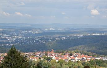 Blick aus großer Höhe über teils flache, teils abgestufte bewaldete Berge. Zwischen den Waldlagen breitet sich eine größere Stadt aus. Im Vordergrund, auf einem Bergsattel, ist ebenfalls eine Ortschaft zu sehen.