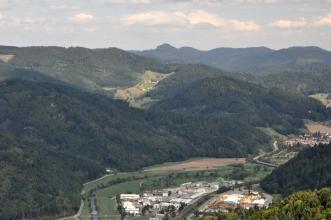 Von erhöhtem Standort aus blickt man rechts unten auf eine Flussaue mit Industriegebäuden sowie sich links daran angrenzende, zahlreiche bewaldete Berge. Im Hintergrund rechts sind weitere Berge erkennbar.