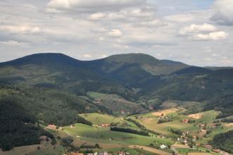 Blick in ein breites Kerbtal mit Wiesen, Äckern und einzelnen Häusern. An den Rändern des Tales erheben sich bewaldete Berge.