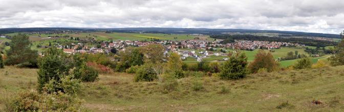 Weiter Blick über einen mit trockenem Gras sowie Bäumen und Sträuchern bedeckten Hügel. Der Hügel fällt zum Hintergrund hin ab. Dahinter öffnet sich eine flache Landschaft mit Äckern, Waldflächen und Siedlungshäusern.