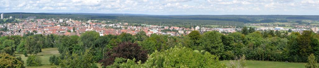 Aus großer Höhe blickt man über Waldstreifen sowie eine größere Siedlung. Im Hintergrund sind bewaldete Höhen, rechts auch flacheres Gelände zu erkennen.