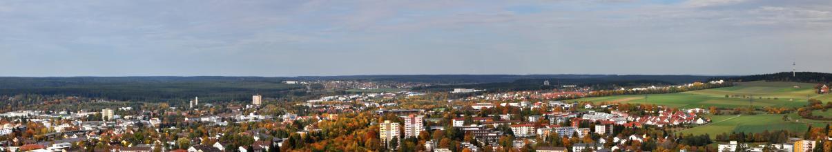 Von bewaldeten Höhenzügen und Hügelkuppen im Hintergrund reicht der Blick nach vorn, wo eine wellige Acker- und Grünlandschaft rechts an eine größere Siedlung links und im Vordergrund grenzt.