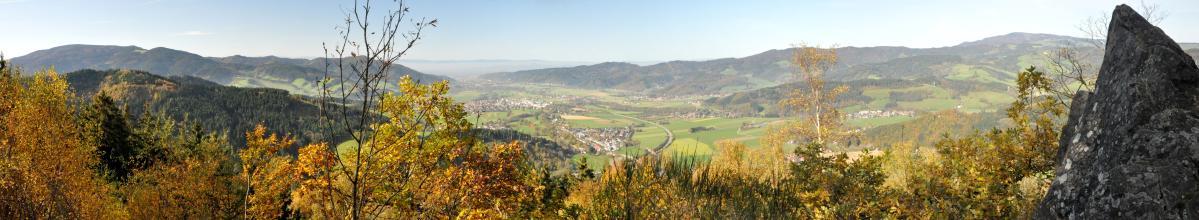 Über Baumwipfel blickt man in ein tiefes, von bewaldeten Hügeln und Bergen umschlossenes Tal. Mehrere Ortschaften sind in diesem Tal verstreut. Rechts am Bildrand ragt ein steiler, dunkler Fels mit dreieckiger Spitze auf.