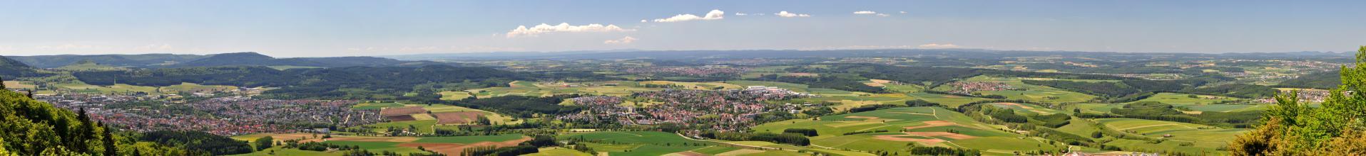 Weiter Blick auf eine hügelige Landschaft mit Wiesen, Feldern, Siedlungen und ausgedehnten Waldflächen. Zum Hintergrund hin reihen sich bewaldete Hügel- und Bergketten aneinander.
