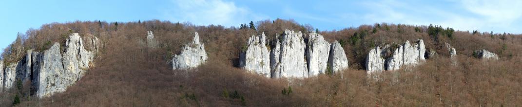 Entlang eines langgezogenen, bewaldeten Bergrückens ragen mehrere weißlich graue Felsspitzen und Felstürme hervor.