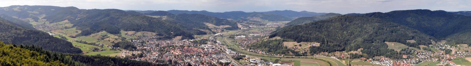 Panoramabild eines breiten Flusstales mit mehreren Siedlungen sowie links und rechts angrenzenden, bewaldeten Höhen.