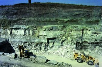 Blick von oben auf eine Steinbruchwand mit grünlichen Gesteinsschichten rechts und dunkler Auflage darüber. Im unteren Bildteil sind Bagger und Radlader zu sehen.