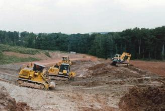 Das Bild zeigt den Abbau in einer Tongrube. Mehrere Raupenfahrzeuge links sowie ein Bagger rechts sind dabei auf einem Hügel im Vordergrund im Einsatz. Ein Waldstreifen im Hintergrund begrenzt das Abbaugelände.