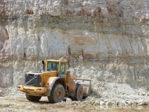 Blick auf eine Steinbruchwand mit drei aufeinanderliegenden, durch graugrüne Streifen getrennte Schichten. Die Farbe des Gesteins ist ein weißliches Grau, oben sind jedoch auch violette Farbtöne zu sehen. Im Vordergrund ein gelber Radlader.