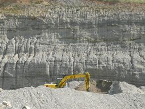 Blick auf eine bildfüllende Steinbruchwand. Dem grau bis bräunlich gefärbten, zahnartig gefurchtem Gestein ist eine Abraumhalde mit Bagger vorgelagert.