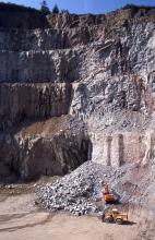 Das Bild zeigt eine mächtige, hohe Steinbruchwand mit mehreren Sohlen. Die linke Seite des Bruches liegt dabei im Schatten. Rechts unten, am Fuß der Wand und neben einem Abraumhügel, arbeiten Bagger und Radlader.