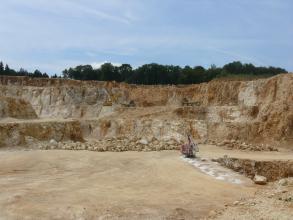 Blick in einen Steinbruch aus hellem, teilweise bräunlich angewittertem Gestein, welches in mehreren Sohlen abgebaut wird. Im Bereich der Tiefsohle finden Bohrarbeiten statt, das Bohrmehl ist weiß.