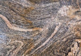 Nahaufnahme einer Gesteinsoberfläche mit wellenartigen Mustern in rosa, grau und dunkelgrau. Dazwischen treiben rötlich braune Schlieren.