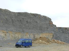 Blick auf eine hohe Abbauwand in einem Steinbruch. Das untere Viertel besteht aus gelblich-beigen gebankten Gesteinen, darüber befindet sich dunkelgraues bis blaugraues Gestein. Vor der Wand steht ein blauer Van.