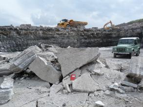 Blick auf Sohle und hintere Wände eines Steinbruches. Im Vordergrund liegen helle Gesteinsbrocken über- und aufeinander. Rechts steht ein Jeep. Im Hintergrund, auf der nächsten Sohle, sind ein Bagger sowie ein Ladefahrzeug erkennbar.