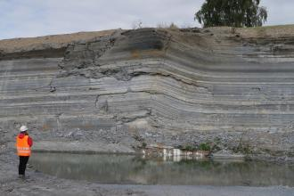 Gezeigt wird die Abbauwand eines Steinbruches. Die dünnen, von hellgrau über dunkelgrau bis braun gefärbten Lagen machen rechts der Bildmitte einen wellenförmigen Knick.