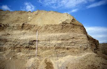 Blick auf eine Abbauwand mit Kies- und Sandlagen. Die oben gerundete Wand fällt nach rechts ab. Links der Bildmitte ist eine Messlatte angelehnt.