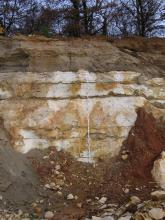 Blick auf eine Abbauwand. Das obere Drittel besteht aus braun-grauen Kiesen und Sanden, die unteren zwei Drittel aus hellem, dickbankigem Kalkstein. Vor der Wand befindet sich ein Maßstab.