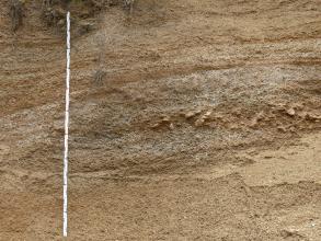 Teilansicht einer Kiesgrube. In der rötlich braunen Abbauwand, innerhalb einer ovalen Linse, liegen Schutt und größere Steine an.