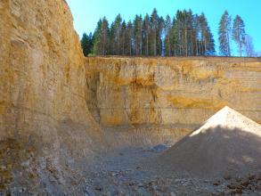 Der Betrachter befindet sich in einem Steinbruch und blickt links und geradeaus auf zwei Steinbruchwände aus hellem, gelblich angewittertem, bankigem Gestein. Auf der Sohle des Steinbruchs befindet sich eine Aufschüttung aus abgebautem Material.