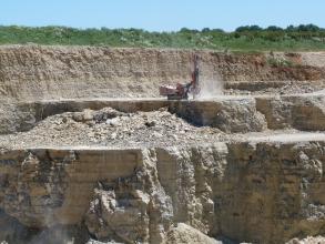Blick auf mehrere Stufen eines Steinbruchs. Das gebankte Gestein ist bräunlich grau bis grau.