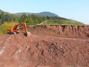 Im Vordergrund des Bildes sieht man eine Abbauwand einer Tongrube. Das rötliche Material wird gerade mit einem Bagger am linken Bildrand abgebaut. Im Hintergrund befinden sich bewaldete Hügel.