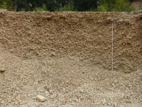 Teilansicht einer Kiesgrube. Zu sehen ist eine rötlich braune, etwa drei Meter hohe Wand sowie im Vordergrund gehäufter Kies und Schutt.