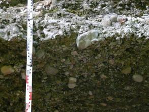 Das Bild zeigt eine durch Licht und Schatten geteilte Erdschicht mit Gesteinslagen unterschiedlicher Größe.