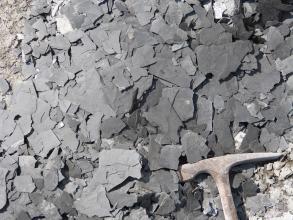 Das Bild zeigt viele kleine, kantige Scherben eines dunkelgrauen, homogenen Gesteins. In der rechten unteren Ecke befindet sich ein Hammerkopf als Maßstab.