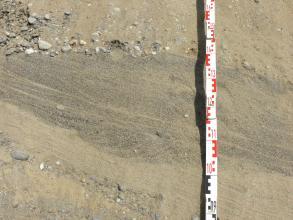 Großaufnahme von hellbraunem bis grauem, schräg nach rechts unten verlaufendem Sand. Oben und unten sind Kieseinschlüsse erkennbar. Rechts ist ein Maßstab angelehnt.