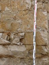 Detailaufnahme einer Abbauwand eines Kalksteinbruchs. Das Gestein ist hellbeige und dickbankig. Vor der Wand befindet sich rechts ein Maßstab.