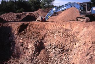 Blick auf die oberste Sohle eines Steinbruches. Das rötliche Gestein ist teilweise zerklüftet und abgerutscht. Oben sind Halden aufgeschichtet, rechts davon steht ein blauer Bagger.