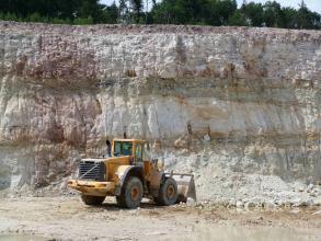 Blick auf eine Steinbruchwand mit drei aufeinanderliegenden, durch grünliche Streifen getrennte Schichten. Die Farbe des Gesteins ist ein weißliches Grau, links sind jedoch auch violette Farbtöne zu sehen. Im Vordergrund ein gelber Radlader.