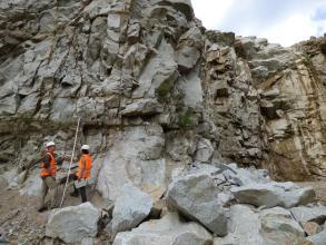 Blick auf eine stark geklüftete Abbauwand eines Steinbruchs. Das Gestein ist mittelgrau. Links unten vor der Wand stehen zwei Menschen in orangenen Warnwesten. Im Vordergrund liegen einige große Gesteinsblöcke.