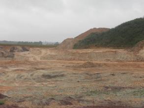 Blick auf eine im Mittelgrund sich erhebende Abbaukante in einer Sandgrube. Im Vordergrund die abgeflachte Grube. Im Hintergrund rechts steigen bewachsene Hügel und Abraumhalden auf.