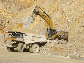 Abbau von hellem Kalkstein in einem Steinbruch. Es befinden sich ein Bagger und ein Laster in der Bildmitte vor der Abbauwand.