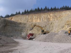 Der Betrachter befindet sich in einem Steinbruch und blickt auf eine mehrere Zehnermeter hohe Abbbauwand aus hellem, gebanktem Kalkstein, an welcher gerade durch Graben und Reißen abgebaut wird.