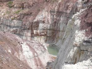 Das Bild zeigt im Hintergrund sowie rechts leicht geneigte, weißlich graue bis violette Steinbruchwände. Am Fuß ist eine kleine Wasserfläche erkennbar. Links vorne schieben sich Abraumhügel ins Bild.