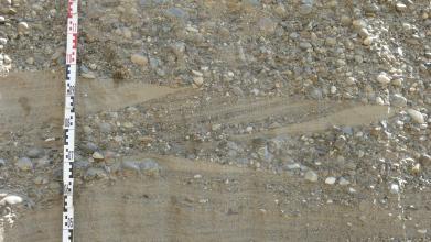 Nahaufnahme mehrerer Schichten von feinem, hellbraunem Sand im unteren Drittel und grobem Kies im oberen Drittel. Die Schicht in der Mitte zeigt sowohl Kies als auch Sand und verläuft schräg zur ansonsten waagrechten Linie.