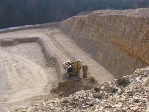 Auf dem Bild ist der Abbau von hellem Gestein auf der oberen Sohle eines Steinbruchs durch einen Bagger zu sehen. Man blickt von erhöhtem Standpunkt in den Steinbruch.