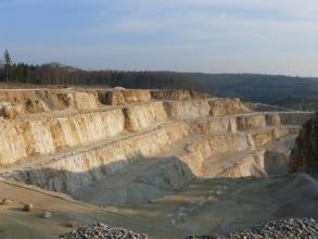 Blick von seitlich oben in einen Steinbruch, in welchem gelbliches Gestein auf mehren Stufen abgebaut wird. Das Gestein leuchtet in der tiefstehenden Sonne, die vordere Hälfte des Steinbruchs liegt im Schatten.