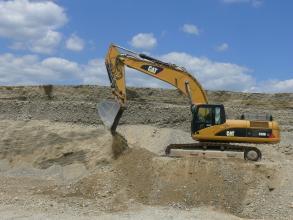 Das Bild zeigt den Kiesabbau in einer Grube. Auf einer erhöhten, flachen Halde rechts vorne arbeitet ein gelber Bagger. Dahinter die hellen Wände der Grube.