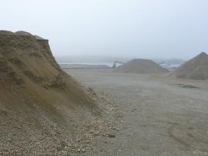Das Bild zeigt größere Kiesberge links vorne und rechts hinten. Die Berge stehen auf ebenem, trockenem Boden. Im dunstigen Hintergrund sind ein See sowie Förderbänder zu erkennen.
