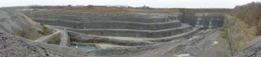 Übersichtsaufnahme eines Steinbruchs, in welchem gräuliches Gestein auf meheren Sohlen abgebaut wird.