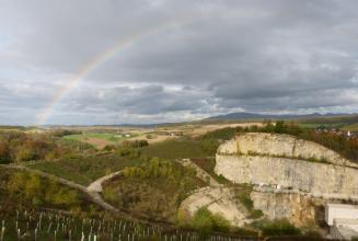 Blick von erhöhtem Standpunkt in einen Steinbruch, welcher sich zur rechten Bildseite hin öffnet. Um den Steinbruch herum befindet sich idyllische Landschaft. Über dem Steinbruch erstreckt sich ein Regenbogen.