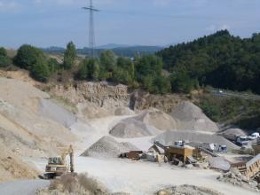 Blick von erhöhtem Standpunkt auf Aufbereitungsanlagen und Lagerhalden im einem Steinbruch. Im Hintergrund befindet sich Wald und ein Strommast.